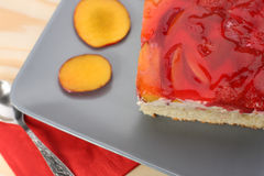 Strawberry and peach cake with gelatin on grey plate on wooden t Stock Photo