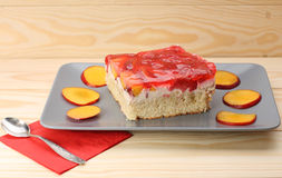 Strawberry and peach cake with gelatin on grey plate on wooden t Royalty Free Stock Photos