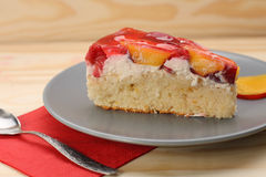 Strawberry and peach cake with gelatin on grey plate on wooden t Stock Images