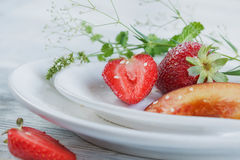 Strawberry and peach with mint. On a white heard shape plate Royalty Free Stock Photography