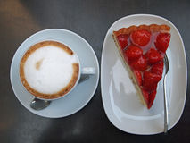Strawberry pie and Cappuccino. A fresh piece of Strawberry pie and a cup of Cappuccino (focus on pie Royalty Free Stock Photos
