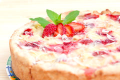 Strawberry pie decorated with ripe strawberry. Close up of a strawberry pie decorated with ripe strawberry, mint and almond flackes Royalty Free Stock Photography