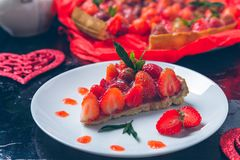 Strawberry pie on white plate black wooden table. One piece.  Romantic. Love. Heart. Toned photo. Valentine Day Stock Photography
