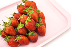 Strawberry pile. Red strawberry put a pile on a pink tray with white background Royalty Free Stock Photos