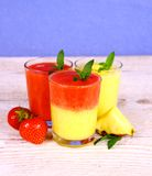 Strawberry and pineapple smoothie in glass on blue background Stock Images