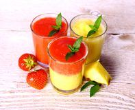 Strawberry and pineapple smoothie in glass with fruits, mint Stock Images