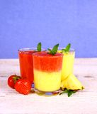 Strawberry and pineapple smoothie mixed on blue background Stock Photos