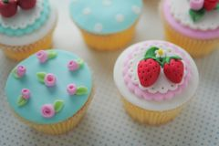 Strawberry fondant cup cakes. Strawberry and pink rose fondant cup cakes royalty free stock images