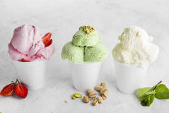 Strawberry, pistachio and vanilla ice cream in disposable cup on Stock Photo