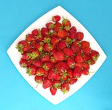 Strawberry on plate. Ripe red strawberry in form of rhomb on dish on blue Royalty Free Stock Photography