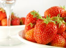 Strawberry in the plate. On the table. Near some one plate with strawberry and glass royalty free stock image