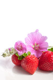Strawberry on a plate decorated with malva flowers. Isolated on white Stock Photo