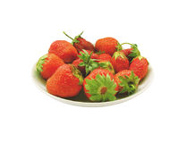 Strawberry on the plate. A few broken red strawberries on a plate on white background Stock Images