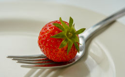 Strawberry on plate with fork Stock Photos