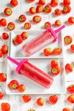 Strawberry popsicles. Made in plastic molds displayed on ceramic plates royalty free stock photo