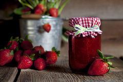 Strawberry Preserves. A pint jar of strawberry preserves, fresh strawberries and steel bucket with strawberry plant blurred in background Royalty Free Stock Photography