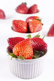 Strawberry ramekin lineup on white background. Fresh berries in ceramic bowls Stock Photos