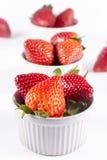 Strawberry ramekin lineup on white background Stock Photos