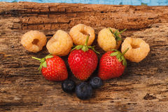 Strawberry, raspberry and blueberry on the old wooden board. Bunch of strawberry, raspberry and blueberry on the old wooden board Stock Photo