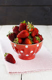 Strawberry in red bowl with a pattern in peas on a fabric napkin. On a white table and one strawberry on table Royalty Free Stock Photos