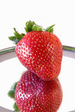 Strawberry and a reflection 0351. A single isolated strawberry reflecting on a shiny surface Royalty Free Stock Photo