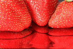 Strawberry Reflection. Reflection of three strawberries in juice Stock Image
