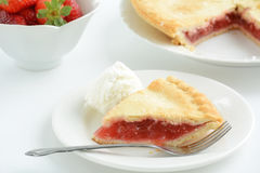 Strawberry rhubarb pie. Fresh baked strawberry rhubarb pie with slice in foreground and ice cream scoop. Shallow depth of field Stock Photography