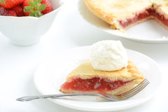 Strawberry rhubarb pie. Fresh baked strawberry rhubarb pie with slice in foreground and ice cream scoop. Shallow depth of field Royalty Free Stock Images
