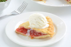 Strawberry rhubarb pie. Fresh baked strawberry rhubarb pie slice with vanilla bean ice cream scoop. Shallow depth of field Stock Images