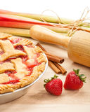 Strawberry Rhubarb Pie. Homemade strawberry rhubarb pie with Strawberries and rhubarb on a wooden cutting board. Traditional late summer/early fall dessert stock image