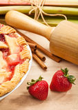 Strawberry Rhubarb Pie. Homemade strawberry rhubarb pie with Strawberries and rhubarb on a wooden cutting board. Traditional late summer/early fall dessert royalty free stock image