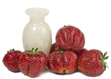 Strawberry, ripe red berries and marble vase Royalty Free Stock Photography