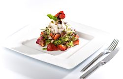 Strawberry salad with fresh goat cheese and mint. With steel fork and knife Royalty Free Stock Image