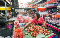 Strawberry saleswoman arranges items on the counter of vibrant street market Royalty Free Stock Photos