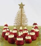 Strawberry santas with christmas tree. Santa figures made from fresh strawberries and cream gathered on a plate with gold christmas tree Stock Photos