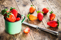 Strawberry scattered around the old wooden table. Stock Photo