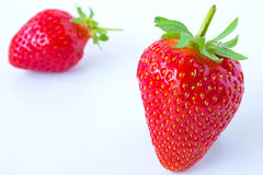 Strawberry Season. Two red strawberries on a white surface,photography Royalty Free Stock Image