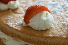 A strawberry segment on a dollop of whipped cream. royalty free stock images