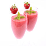 Strawberry shakes. Strawberry shake in champagne glasses decorated with a strawberry and mint Stock Image