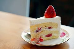 A strawberry shortcake topped with a large fresh strawberry placed in white plate and on wooden table with copy space. Victorian sponge cake with cream and Stock Image