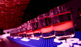 Strawberry Shots On The Line. Red Strawberry Drink Shots On The Line with 3 colourfull layers waiting for the customers in the club Stock Photo