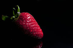Strawberry single with drops. Isolated on black royalty free stock image