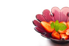 Strawberry slice and mint in purple flower shape bowl on white background Royalty Free Stock Photography