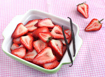 Strawberry slices in bowl with vanilla bean Royalty Free Stock Images