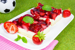 Strawberry slices with soccer ball on grass Stock Image