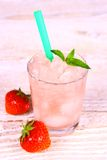 Strawberry slush in glass with straw and berries Royalty Free Stock Images