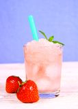 Strawberry slush in glass with straw on blue background Stock Image