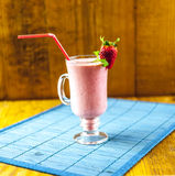 Strawberry smoothie. On blue and wooden background Stock Images
