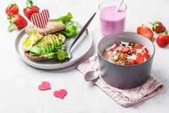 Strawberry smoothie bowl with granola, coconut, berries and avocado toast on a white background. Valentine`s Day concept stock photos