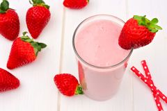 Strawberry smoothie, downward view over white wood Royalty Free Stock Photography